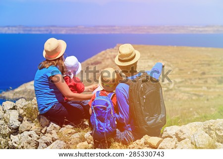 family with two kids looking at map in mountains, family travel - stock photo