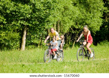 Family with two kids riding their bicycles on a summer day - stock photo