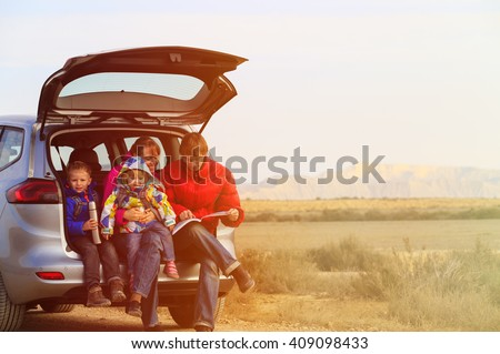 family with two kids travel by car in mountains - stock photo
