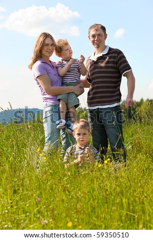 Family with two little boys playing in the grass on a summer meadow carrying one of the kids - stock photo