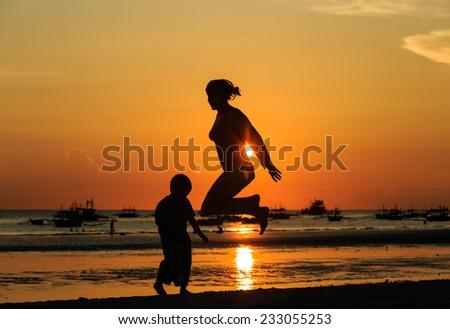 famiy jumping at sunset beach - stock photo