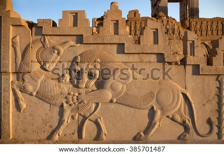 Famous bas relief carving of a lion hunting a bull in Persepolis World Heritage Site, which used to decorate the wall of kingdom palace in Achaemenid Empire, 500 BC. - stock photo