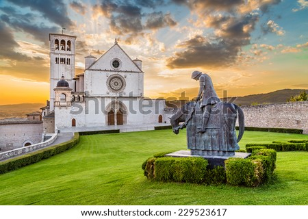 Famous Basilica of St. Francis of Assisi (Basilica Papale di San Francesco) with statue at sunset in Assisi, Umbria, Italy - stock photo