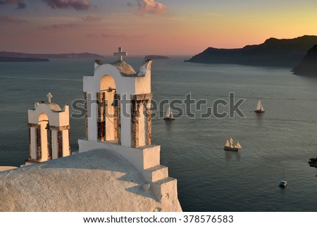 Famous bell towers in the island of Santorini, Greece at sunset - stock photo