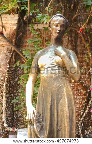 Famous bronze statue of Juliet Capulet standing in front of Juliet Balcony, in Verona, Italy. It's believed that if touch on Juliet's right breast, they will be blessed in their love life. Warm toned. - stock photo