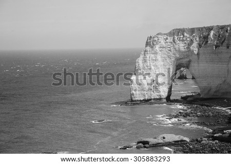 Famous chalk cliffs at Cote d'Albatre (Alabaster Coast). Etretat, France. Aged photo. Black and white. - stock photo