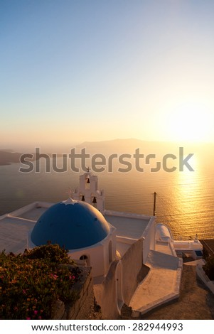 Famous church in Fira, Santorini at sunset with a perfect view of the volcano - stock photo