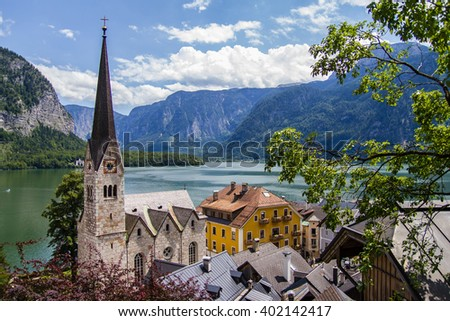 Famous Hallstatt mountain village with Hallstaetter Lake in the Austrian Alps, Austria. Beautiful view from above on the village, stone church, Alpine lake, rooftops of houses and mountains. Sunny day - stock photo