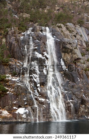Famous Hengjanefossen waterfall coming down from a steep rock face into Lysefjord, Norway - stock photo