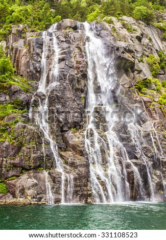 Famous Hengjanefossen waterfall coming down from a steep rock face into Lysefjord, Rogaland, Norway - stock photo