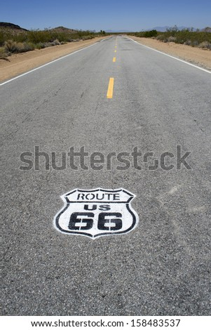 Famous historic Route 66 pavement sign with Mojave desert - stock photo