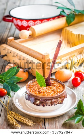Famous italian ragu bolognese meat sauce and the utensils for making fresh home-made pasta - stock photo