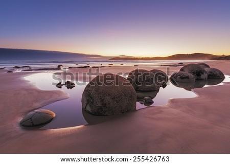 Famous Moeraki Boulders at sunrise, Koekohe beach,Otago, South Island, New Zealand - stock photo
