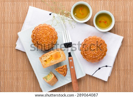 Famous moon cake with assorted nuts and egg yolk. Mooncake and tea,Chinese mid autumn festival food. angle view from above - stock photo