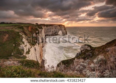 Famous natural arch in Etretat (Normandy, France) at sunset. - stock photo