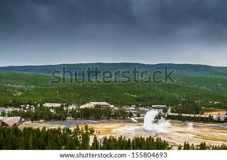 Famous Old Faithful Geyser while erupting taken from the Overlook during stormy weather - stock photo
