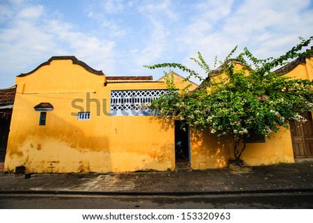 Famous old yellow wall with paper flower at Hoi An Ancient Town in early morning sunshine, Quang Nam, Vietnam. Hoi An is recognized as a World Heritage Site by UNESCO. - stock photo