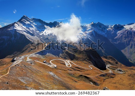 Famous picturesque views of the road in Austrian Alps - Grossglocknershtrasse. The highest mountain peaks covered with fresh snow. Ideal highway winds high in the mountains - stock photo