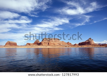 famous red cliffs reflected in the smooth water of the lake Powell - stock photo