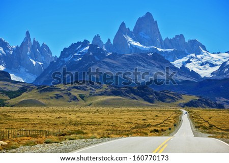 Famous rock Fitz Roy peaks in the Andes. Magnificent panorama of snow-capped mountains in Patagonia. To mountains leads the asphalt road - stock photo