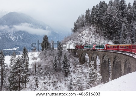 Famous sightseeing train running over viaduct in Switzerland, the Glacier Express in winter - stock photo