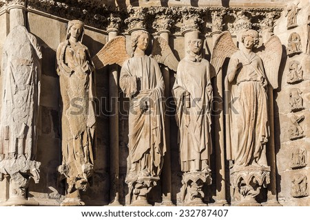 Famous smiling angel (right) on Notre-Dame de Reims cathedral facade (Our Lady of Reims, 1275), Reims, France. Reims Cathedral is seat of the Archdiocese of Reims, where kings of France were crowned. - stock photo