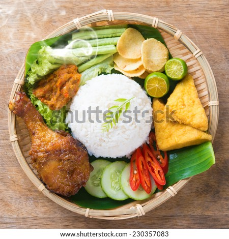 Famous traditional Indonesian food. Delicious nasi ayam penyet with sambal belacan. Fresh hot with steam smoke. - stock photo