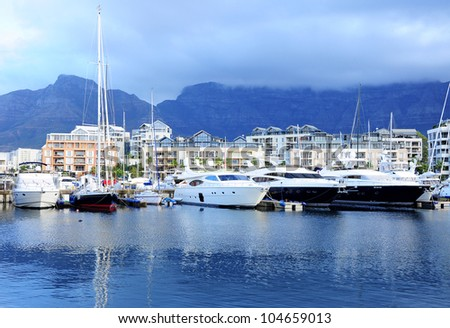 Famous V&A waterfront of Cape Town with table mountain background on the cloudy day - stock photo