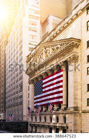 Famous Wall street and the building in New York, New York Stock Exchange with patriot flag - stock photo