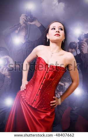 famous woman posing away from paparazzi - stock photo