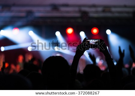 Fan concert recording. Crowd with his hands in the air and flares. - stock photo