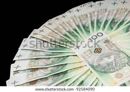 Fan of one hundred polish zloty paper banknotes lying on black background, horizontal orientation, nobody. - stock photo
