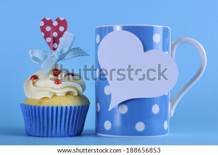Fancy blue theme cupcake with red and white decorations with heart topper and polka dot coffee mug for birthday or special occasion gift on pale blue background. - stock photo