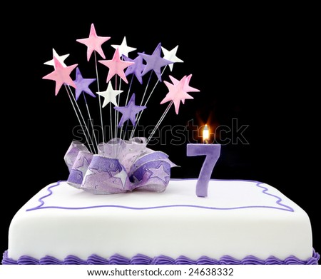 Fancy cake with number 7 candle.  Decorated with ribbon and star-shapes, in pastel tones on black background. - stock photo