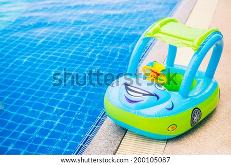Fancy car toy for kids around swimming pool - stock photo