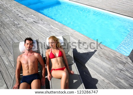 Fancy couple relaxing in longchairs by swimming pool - stock photo