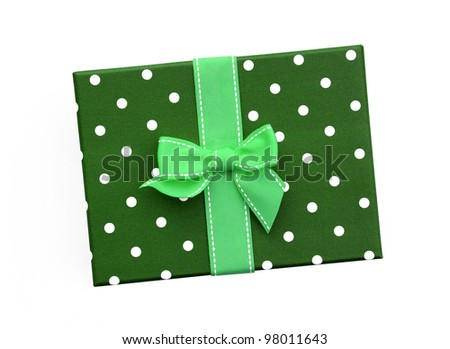 Fancy green ribbon gift bow with white stitching on green gift box with polka dots isolated on white background - stock photo