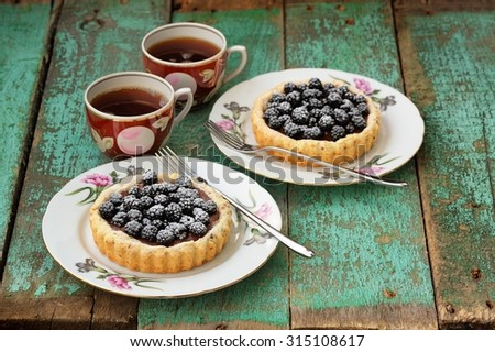 Fancy homemade cakes with fresh blackberries and chocolate cream decorated with icing sugar with two cups of black tea on old wooden board  horizontal - stock photo