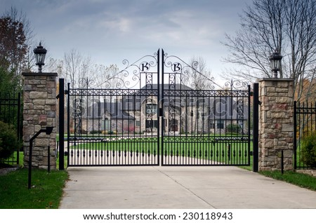 fancy large mansion behind a locked gate - stock photo