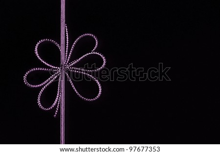 Fancy purple ribbon bow isolated on black background with room for your text - stock photo