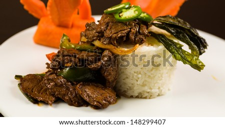 Fancy sliced Asian pepper steak served with white rice and garnished with carved carrot swans on a white plate. - stock photo