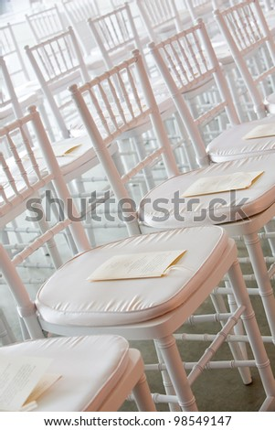 Fancy white chairs set up during a wedding ceremony. There is paper with the schedule on it. You cannot read the words. - stock photo