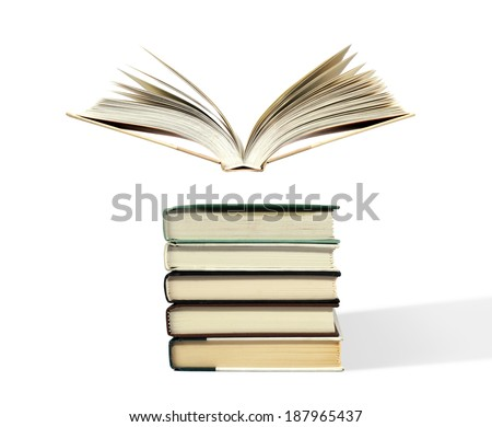 Fanned book floating above stack - stock photo