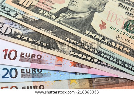 Fanned out banknotes of euros and dollars. Closeup. - stock photo