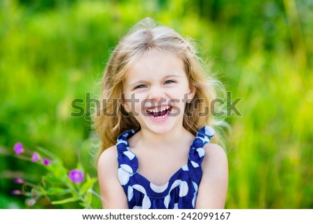 Fanny and beautiful laughing little girl with long blond curly hair, outdoor portrait in summer park on bright sunny day. Child in green grass field with purple flowers. Closeup portrait. - stock photo