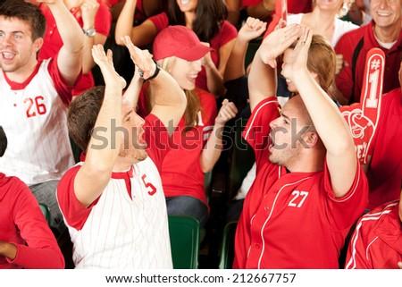 Fans: Baseball Fans Do High Five After Home Run - stock photo