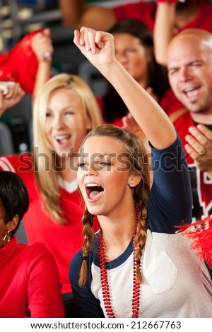 Fans: Girl At Football Game Cheers Loudly For Team - stock photo
