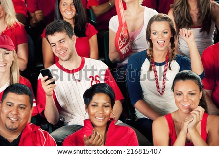 Fans: Mans Checks His Phone For Messages During Baseball Game - stock photo
