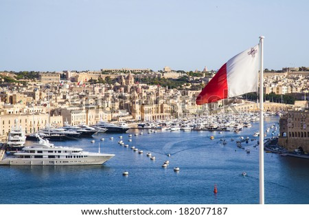 fantastic city landscape on the seaside in Malta.Republic of Malta flag waving in Valletta - stock photo