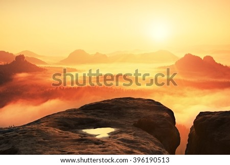 Fantastic dreamy daybreak above peaks of smoky mountain with the view into misty valley. Vivid and vignetting effect. - stock photo